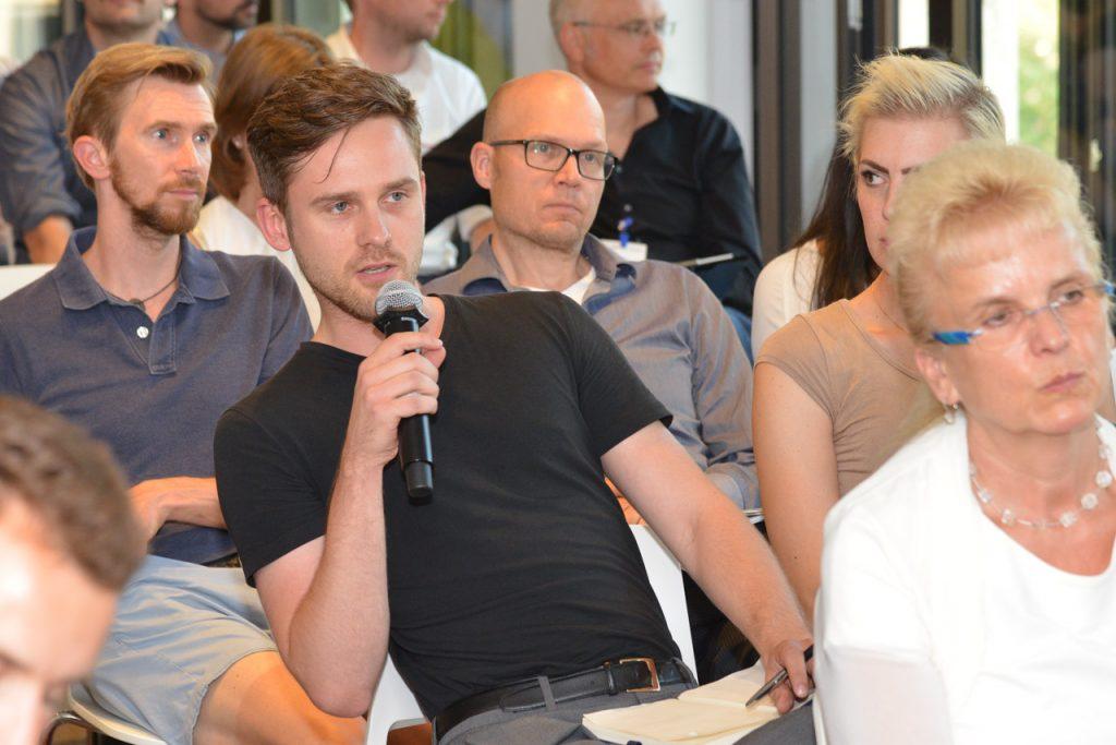 Zuhörer aus dem Publik stellt eine Frage auf der Fachkonferenz ganzheitliches Online Marketing für den Mittelstand