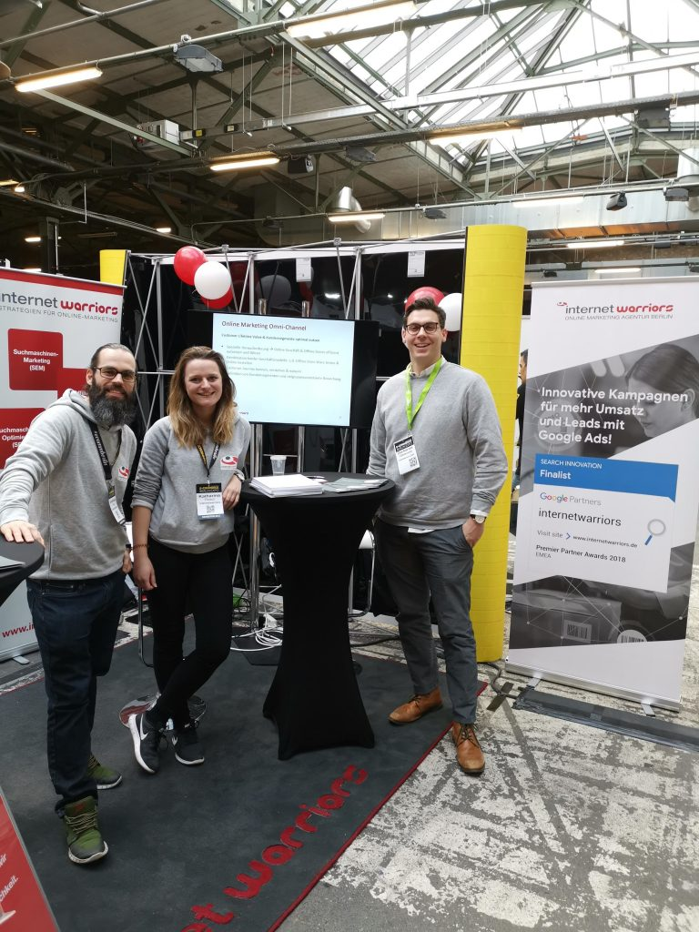 internetwarriors Team auf dem Messestand der Expo Berlni 2019 in grauen Hoodies